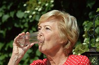 female senior 73 years old sits in the hot sun, enjoys drinking a glass of water
