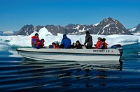 Open motor boat with warm dressed people runs through ice pack Ammassalik Fjord Eastgreenland