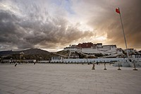The red flag of China flying in Potala Square on a stormy afternoon in front of the Potala Palace, UNESCO World Heritage Site, Lhasa, Tibet, China, As...