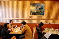Young Chinese People eating Burgers in a Mc Donalt Restaurant in Chinatown