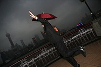 One Caucasian Businessman Jumping With An Opened Umbrella At The Bund,Overcast And Rainy,Shanghai,China