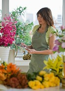 Florist holding clipboard and looking at flowers