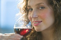 Close up portrait of woman smelling red wine