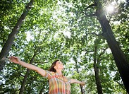 Woman standing below trees with arms outstretched