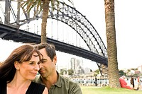 couple (ages 43 and 42) sitting in park near The Rocks and Sydney Harbour Bridge. Sydney, Australia