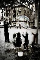 Niños jugando con una gran pompa de jabón, Plaça del Diamant, Barcelona, Espanya