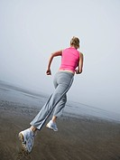 Woman jogging on foggy beach