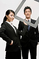 Businessman and woman holding a frame together