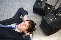 Businessman with luggage resting