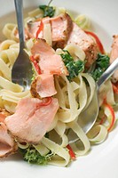 Ribbon pasta with fried peppered salmon close_up