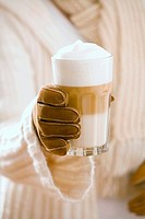 Woman in gloves holding a glass of latte macchiato