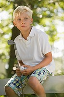 Boy sitting on fence with golf club and ball