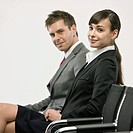 Businesswoman and businessman sitting on chiar, side view