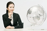 Businesswoman sitting at table with globe