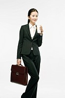 Businesswoman holding coffee and briefcase