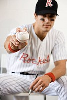 Portrait of baseball player holding autographed baseball