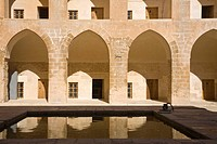 Arched colonnades of Kasimiye Medresi reflecting in courtyard pool, Mardin, Anatolia, Turkey