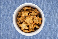 Bird's-eye view of small star-shaped poppy seed crackers sprinkled with sesame seeds, in a white ceramic bowl on a blue background