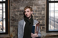 Portrait of a young man holding books