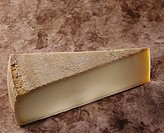 A piece of Gruyere on brown background