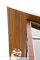 Couple hugging on balcony of modern house (thumbnail)