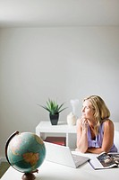 Woman sitting in home office and looking pensive (thumbnail)