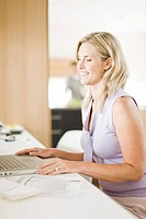 Woman using laptop in home office (thumbnail)