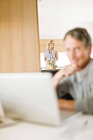 Woman in kitchen watching husband using laptop
