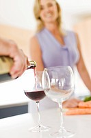 Couple pouring glass of wine in kitchen