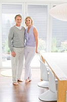 Portrait of couple standing in dining room