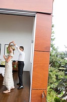 Couple in eveningwear dancing in bedroom (thumbnail)