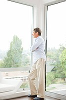 Man leaning against living room window