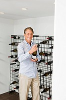 Portrait of man selecting wine from wine rack