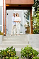 Portrait of couple hugging on front stoop of modern house