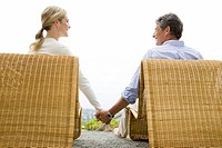 Couple sitting on patio chairs and holding hands