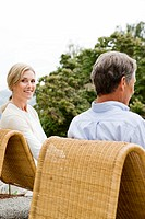 Portrait of couple sitting on patio chairs