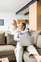 Woman hugging man using laptop in living room