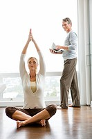 Man holding magazine and woman doing yoga