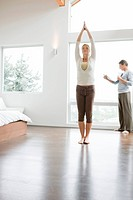 Woman standing in yoga pose and man reading newspaper