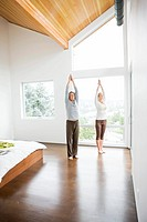 Couple standing in yoga pose in bedroom