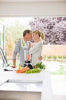 Hugging couple preparing health shake in kitchen