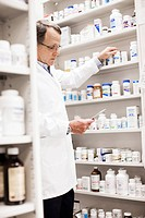 Pharmacist looking at prescription and reaching for pill bottle