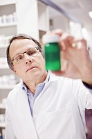 Close up of pharmacist holding green prescription bottle