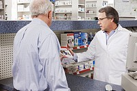 Pharmacist showing blood pressure monitor to customer