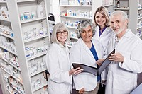 Portrait of four smiling pharmacists holding file (thumbnail)