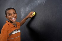 Portrait of a boy wiping a blackboard