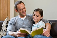 Father and daughter reading a book together (thumbnail)