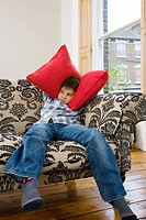 Boy covering his ears with cushions
