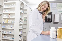 Pharmacist filling prescription and talking on telephone (thumbnail)