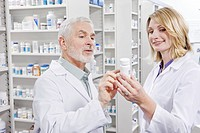 Pharmacists examining label on pill bottle (thumbnail)